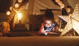 Happy child girl laughing and reading book in dark in tent at ho Royalty Free Stock Photography