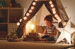 Happy child girl laughing and reading book in dark in tent at ho Stock Photography