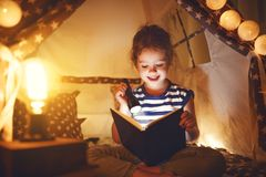 Happy child girl laughing and reading book in dark in tent at ho Royalty Free Stock Photos