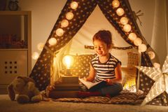 Happy child girl laughing and reading book in dark in tent at ho Stock Image