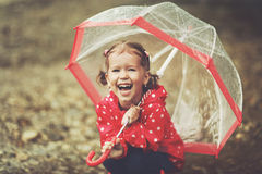 Happy child girl laughing with an umbrella in rain Stock Photos