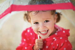 Happy child girl laughing with an umbrella in rain Stock Photo