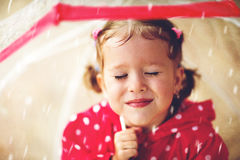 Happy child girl laughing with an umbrella in rain Stock Image