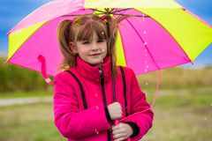 Happy child girl laughing with an umbrella in the rain Stock Photography