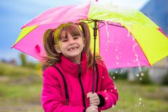 Happy child girl laughing with an umbrella in the rain Royalty Free Stock Photo