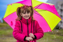 Happy child girl laughing with an umbrella in the rain Royalty Free Stock Images