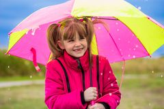 Happy child girl laughing with an umbrella in the rain Royalty Free Stock Photography