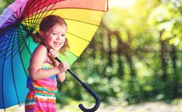 Happy child girl laughs and plays under summer rain with an umbr Stock Photo