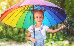 Happy child girl laughs and plays under summer rain with an umbrella. royalty free stock images