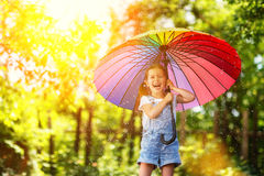Happy child girl laughs and plays under summer rain with an umbrella. Happy child girl laughs and plays under the summer rain with an umbrella royalty free stock image