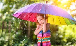 Happy child girl laughs and plays under summer rain with an umbr Royalty Free Stock Images