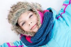 Happy child girl laying down on a frozen clear snow Stock Photography