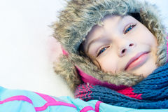 Happy child girl laying down on a frozen clear snow Stock Image