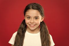Happy child girl with long hair on red background. Happiness and joy. Positive emotions. Child care and upbringing. Kid. Smiling cute face live carefree happy royalty free stock image