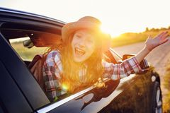 happy child girl looking out the car window during road trip on summer vacations. stock photos
