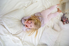 Happy child girl is lying down in the white bed Royalty Free Stock Photo