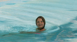 Happy child girl making funny crazy face expression, and swimming in the ocean Stock Images