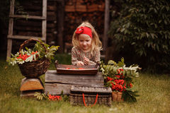 Happy child girl making rowan berry beads in autumn garden Stock Image