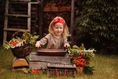 Happy child girl making rowan berry beads in autumn garden Stock Photography