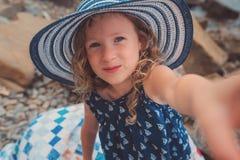 Happy child girl making selfie, cozy summer holidays on seaside Royalty Free Stock Image