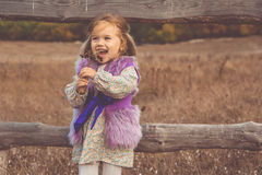 Happy child girl in near wooden fence Stock Image