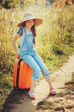 Happy child girl with orange suitcase traveling alone on summer vacation. Kid going to summer camp. Stock Photos