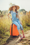 Happy child girl with orange suitcase traveling alone on summer vacation. Kid going to summer camp. Royalty Free Stock Image