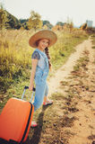 Happy child girl with orange suitcase traveling alone on summer vacation. Kid going to summer camp. Royalty Free Stock Photos