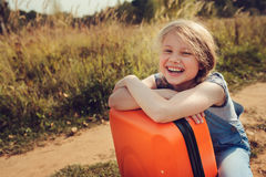 Happy child girl with orange suitcase traveling alone on summer vacation. Kid going to summer camp. Stock Images