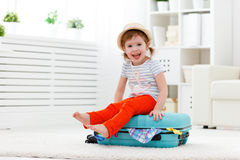 Happy child girl packs clothes into suitcase for travel, vacatio. Happy child girl tourist packs clothes into a suitcase for travel, vacation Stock Photo