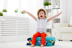 Happy child girl packs clothes into suitcase for travel, vacatio. Happy child girl tourist packs clothes into a suitcase for travel, vacation Royalty Free Stock Image