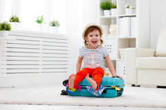 Happy child girl packs clothes into suitcase for travel, vacatio. Happy child girl tourist packs clothes into a suitcase for travel, vacation Royalty Free Stock Photo