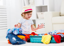 Happy child girl packs clothes into suitcase for travel, vacatio. Happy child girl tourist packs clothes into a suitcase for travel, vacation Royalty Free Stock Photos