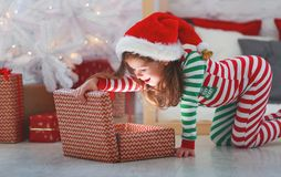 Happy child girl in pajamas with christmas gifts stock photos