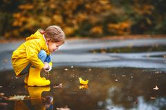 Happy child girl with paper boat in puddle in autumn on natu