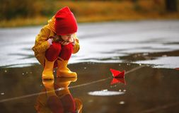 Happy child girl with paper boat in puddle in autumn on nature Royalty Free Stock Photos