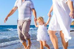 Happy child girl with parents holding hands and having fun walking on the beach. Family vacation, travel concept. Bright sunlight. stock images
