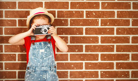 Happy child girl photographer with camera at brick wall royalty free stock image