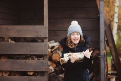 Happy child girl picking firewood from shed in winter Royalty Free Stock Photo