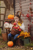 Happy child girl picking fresh apples on the farm. Country living concept. Growing fruits on farm Stock Photos
