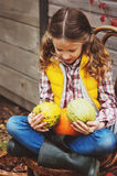 Happy child girl picking fresh apples on the farm. Country living concept. Growing fruits on farm Royalty Free Stock Image