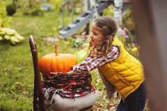 Happy child girl picking fresh pumpkins on the farm. Country living concept Stock Images