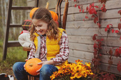 Happy child girl picking fresh pumpkins on the farm. Country living concept. Growing vegetables on farm Royalty Free Stock Image