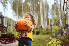 Happy child girl picking fresh pumpkins on the farm. Country living concept Royalty Free Stock Photos