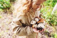 Happy child girl picking wild mushrooms on the walk in summer Stock Photo