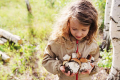 Happy child girl picking wild mushrooms on the walk in summer Royalty Free Stock Photos