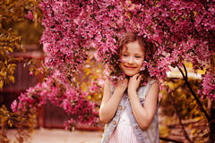 Happy child girl in pink cherry flowers in spring garden Stock Photos