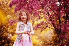 Happy child girl in pink dress playing outdoor in spring garden near blooming crabapple tree Stock Photo