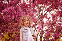 Happy child girl in pink dress playing outdoor in spring garden near blooming crabapple tree Royalty Free Stock Image