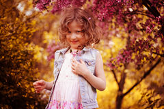 Happy child girl in pink dress playing outdoor in spring garden near blooming crabapple tree Stock Image